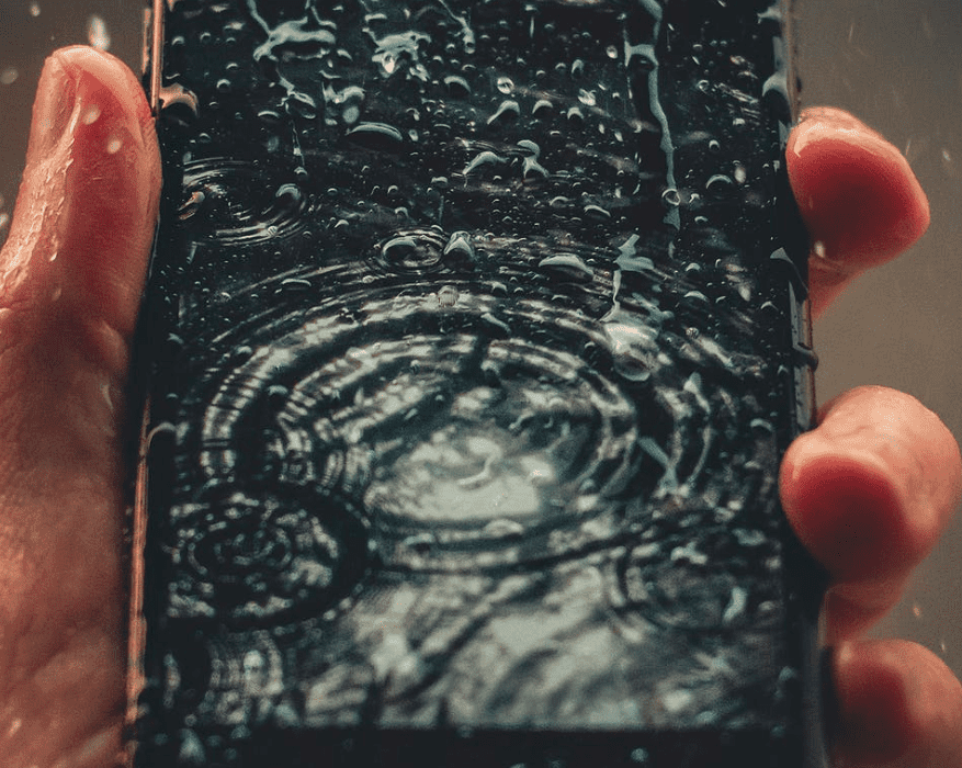 waterproof phone case: person holding wet smartphone