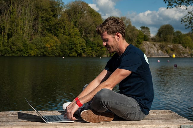 man looking at his laptop outdoors