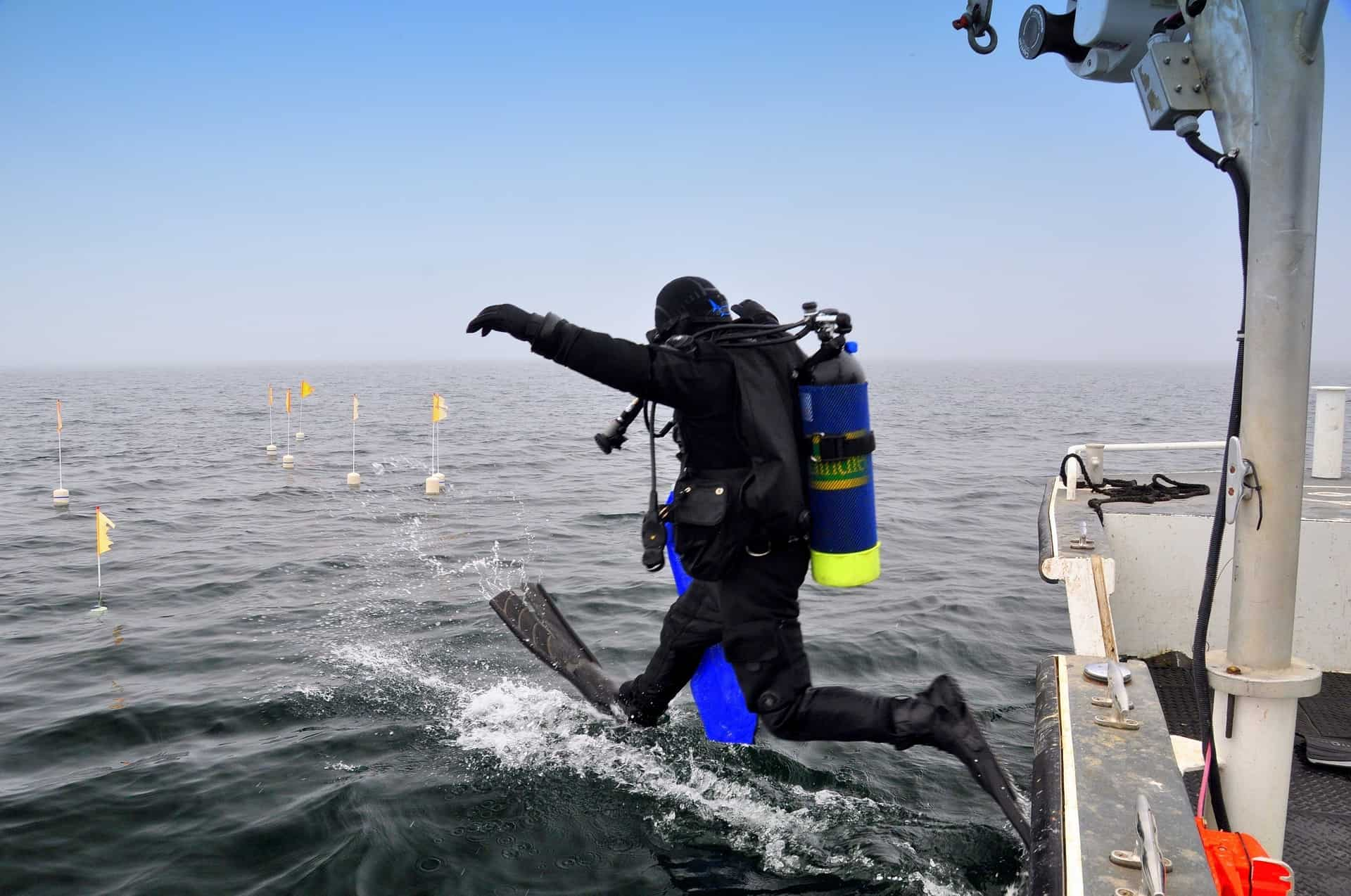 Scuba driver is about to jump at the ocean wearing the best deep sea diving suit